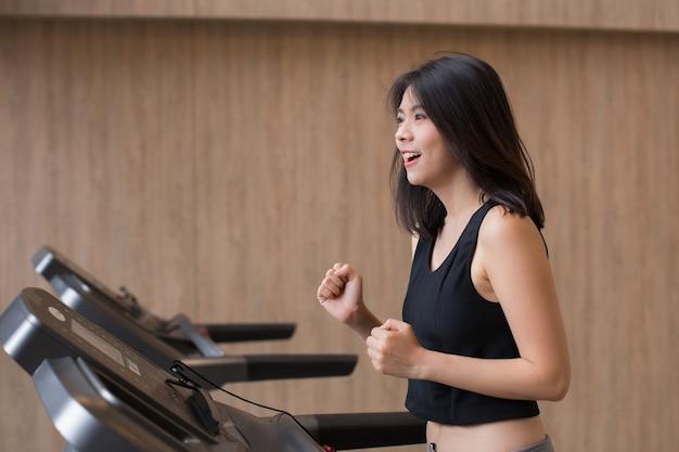 Jonge aziatische vrouwentraining op loopband in gymnastiek