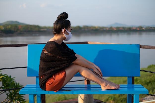 Jonge aziatische vrouwenzitting bij de blauwe bank en het dragen van een medisch masker tegen coronavirus te beschermen