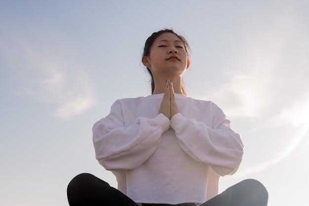 Jonge aziatische vrouwenzitting die bij ochtend mediteren