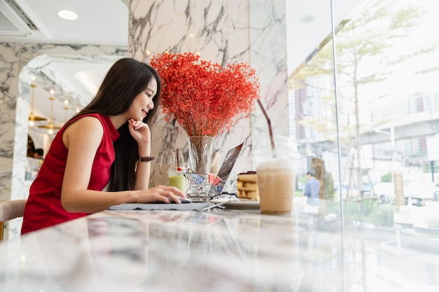 Jonge aziatische vrouwenzitting die gebruikend laptop glimlachen die in koffiewinkel werken