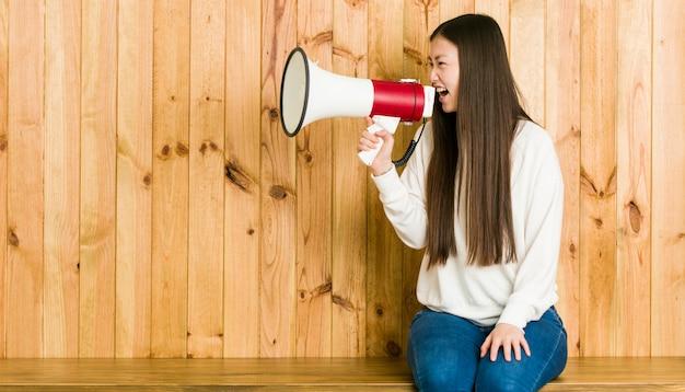 Jonge aziatische vrouwenzitting en het spreken door een megafoon