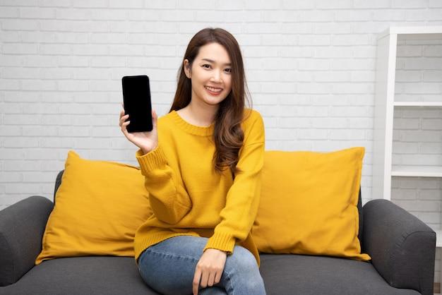 Jonge aziatische vrouwenzitting op bank en het tonen van huidige mobiele telefoontoepassing thuis