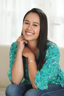 Jonge aziatische vrouwenzitting op laag thuis en glimlachend voor camera