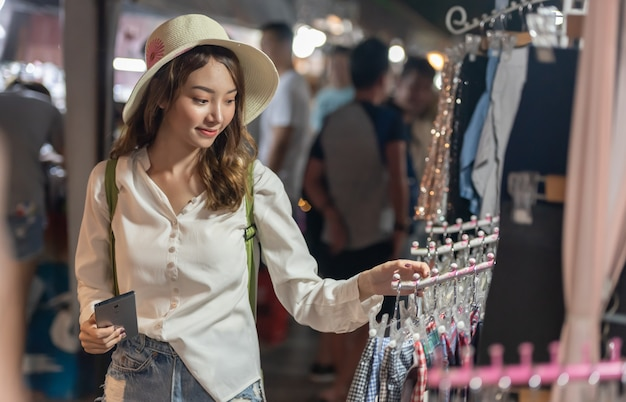 Jonge aziatische winkelende vrouw die en doeken kiezen kopen bij nachtmarkt