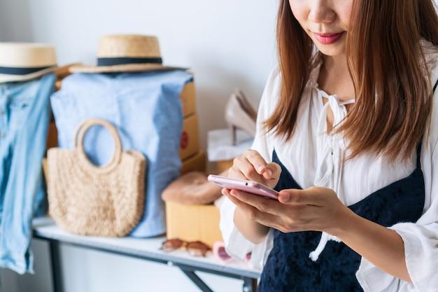 Jonge aziatische zakelijke ondernemer chatten met klant via smartphone