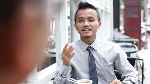 Jonge aziatische zakenlieden die buiten bespreken