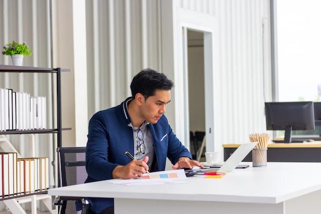 Jonge aziatische zakenlieden die op het benoemingsboek in het bureau letten
