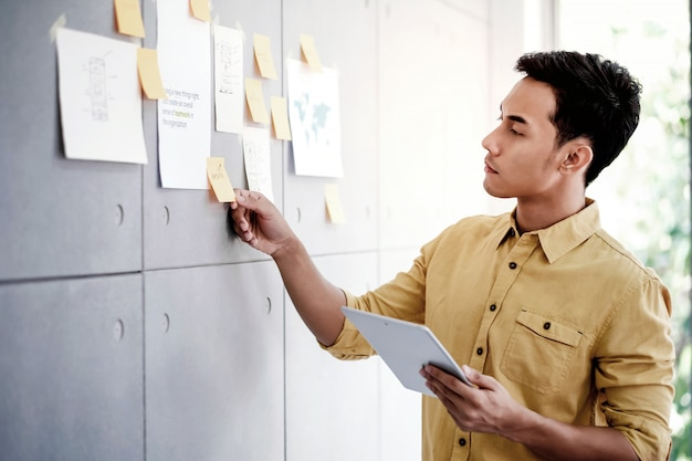 Jonge aziatische zakenman die aan digitale tablet in bureauvergaderzaal werken