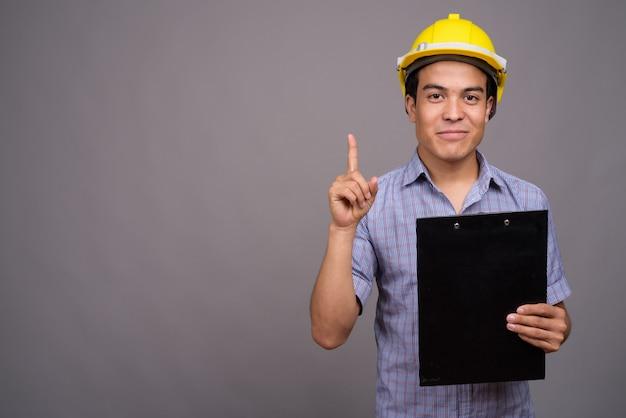 Jonge aziatische zakenman die bouwvakker draagt terwijl het klembord tegen de grijze muur
