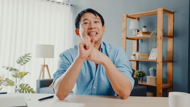 Jonge aziatische zakenman die computerlaptop gebruikt, praat met collega's over plan in videogesprekvergadering tijdens het werken vanuit huis