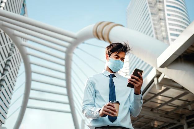 Jonge aziatische zakenman die een chirurgisch masker draagt en een slimme telefoon in stad gebruikt.