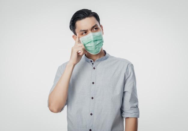 Jonge aziatische zakenman die een hygiënisch masker draagt en denkt om infectie, 2019-ncov of coronavirus te voorkomen. luchtwegaandoeningen zoals pm 2,5 vechten en griep geïsoleerd op een witte muur