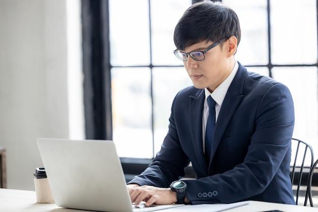 Jonge aziatische zakenman die een laptopcomputer gebruikt die werkt en een videoconferentievergadering houdt, jonge aziatische creatieve man die op een computerlaptop kijkt.