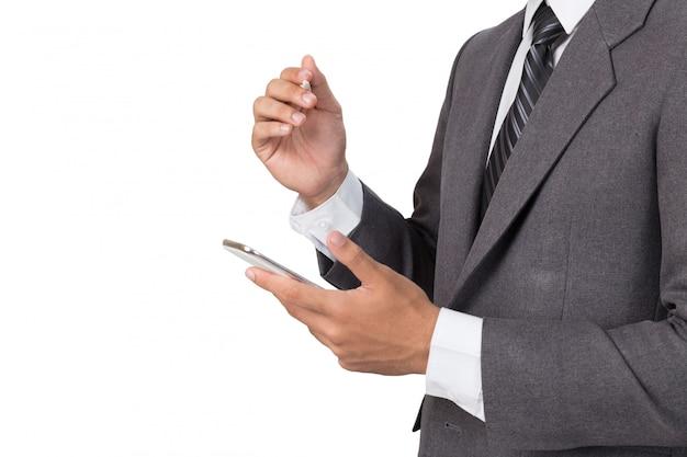 Jonge aziatische zakenman die grijs kostuum dragen die mobiele slimme telefoon met aanrakingspen gebruiken over witte muur