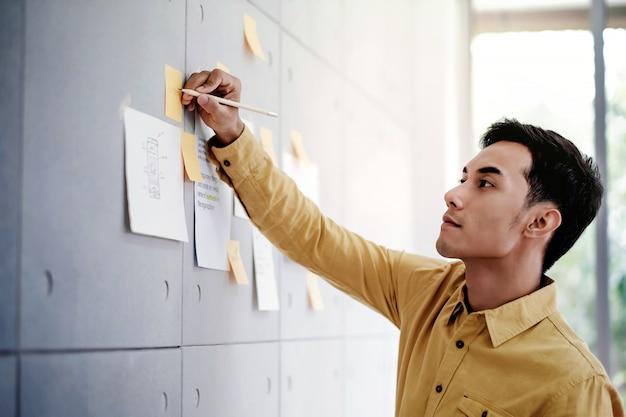 Jonge aziatische zakenman die in bureauvergaderzaal werkt
