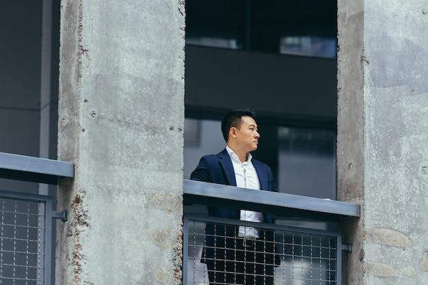 Jonge aziatische zakenman die in de buurt van een modern zwart kantoorgebouw van beton staat, op een balkonterras met kolommen