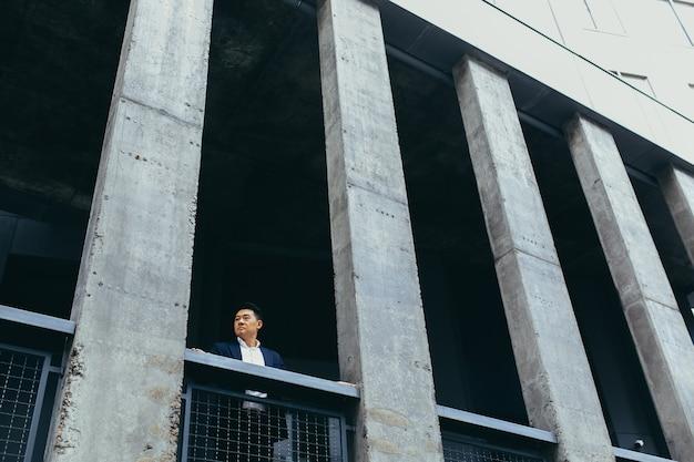 Jonge aziatische zakenman die in de buurt van een modern zwart kantoorgebouw van beton staat, op een balkonterras met kolommen Premium Foto