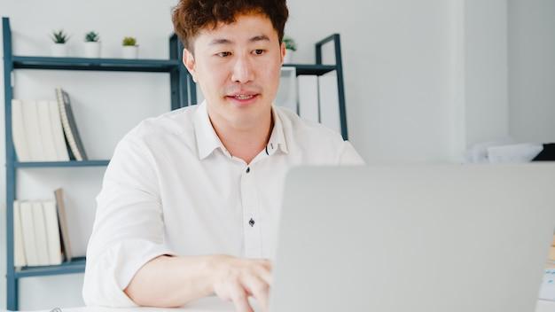 Jonge aziatische zakenman die laptop gebruikt, praat met collega's over plan in videogesprek
