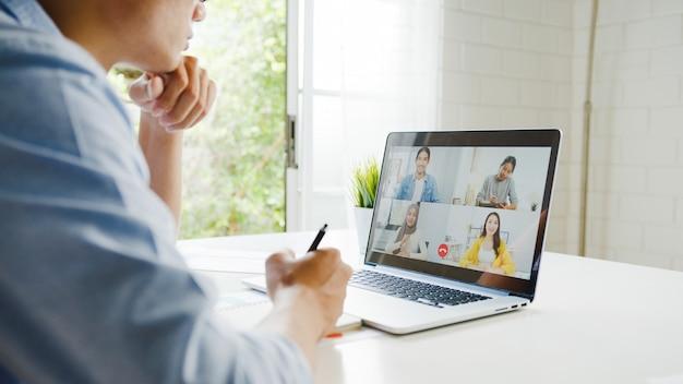 Jonge aziatische zakenman die laptop met behulp van praat met collega's over plan in videogesprekvergadering terwijl het werken vanuit huis in de woonkamer. zelfisolatie, sociale afstand nemen, quarantaine voor coronaviruspreventie.