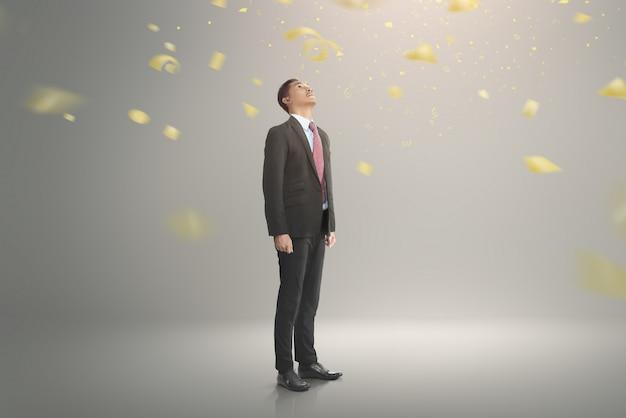Jonge aziatische zakenman die omhoog met dalende confettien kijkt