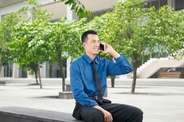 Jonge aziatische zakenman die op de telefoon spreekt