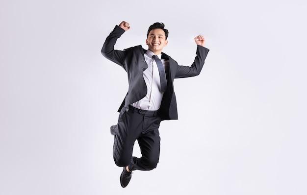 Jonge aziatische zakenman die op wit springt