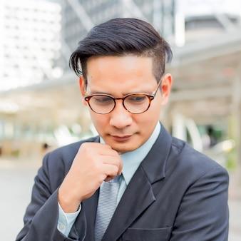 Jonge aziatische zakenman die over zijn zaken denkt