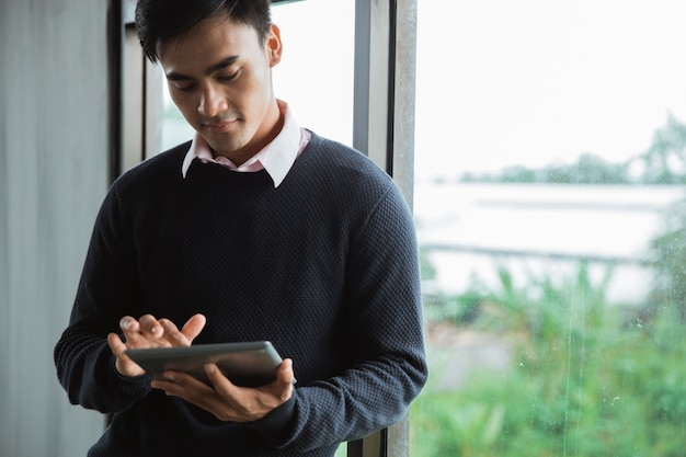 Jonge aziatische zakenman die tablet gebruiken