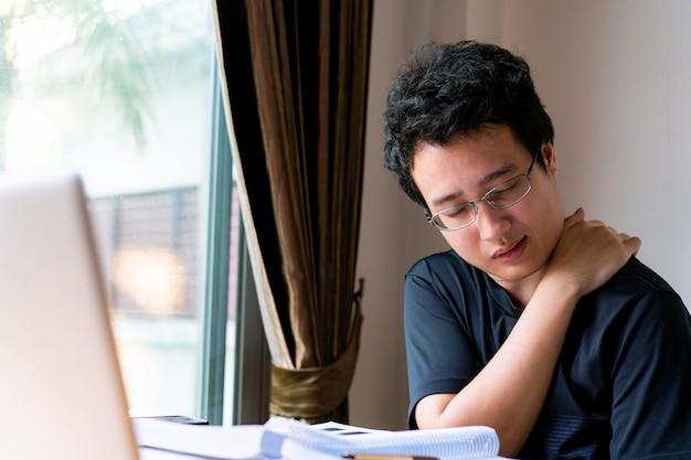 Jonge aziatische zakenman die thuis werkt en gezondheidsprobleem heeft, voelt hij pijnlijk op zijn lichaam van de kwestie van het kantoorsyndroom. lang werken kan pijn aan de schouder veroorzaken. man maakte zich zorgen over zijn gezondheid.