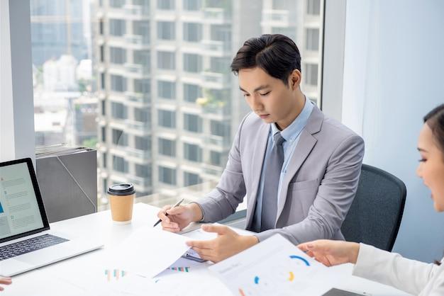 Jonge aziatische zakenman die zich bij het lezen van document in de vergadering concentreert