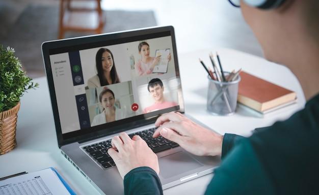 Jonge aziatische zakenman draagt een koptelefoon die op afstand werkt vanuit huis en virtuele videoconferentievergaderingen met collega's uit het bedrijfsleven. sociale afstand thuis kantoor concept.