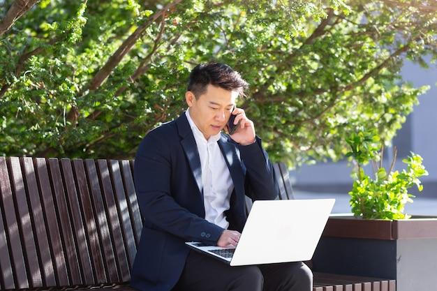 Jonge aziatische zakenman, freelancer zittend op een bankje, werken met laptop in stadspark op moderne stedelijke straat achtergrond buitenshuis in het centrum man geniet van buiten ondernemer praten op mobiele telefoon