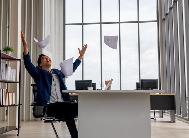 Jonge aziatische zakenman gefeliciteerd en gooide de documenten papier vliegt in de lucht.
