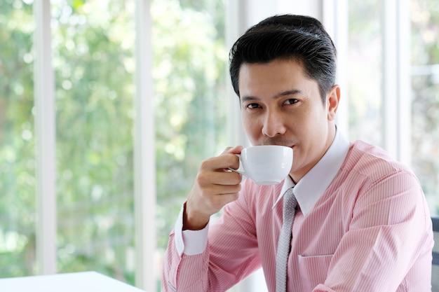 Jonge aziatische zakenman het drinken koffie op kantoor