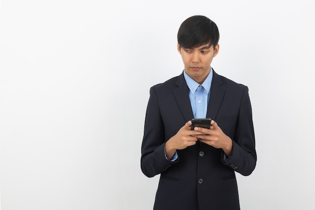 Jonge aziatische zakenman in zwart kostuum die smartphone gebruiken die op witte achtergrond wordt geïsoleerd, online online, op afstand werkend