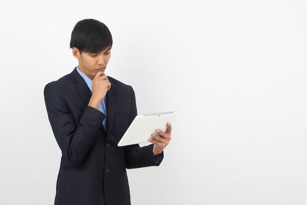 Jonge aziatische zakenman in zwart kostuum die tabletcomputer met behulp van die op witte achtergrond wordt geïsoleerd, online online, op afstand werkend