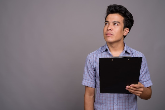 Jonge aziatische zakenman klembord houden tegen grijze muur