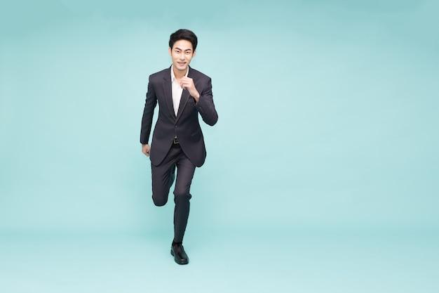 Jonge aziatische zakenman loopt vooruit geïsoleerd op groene achtergrond