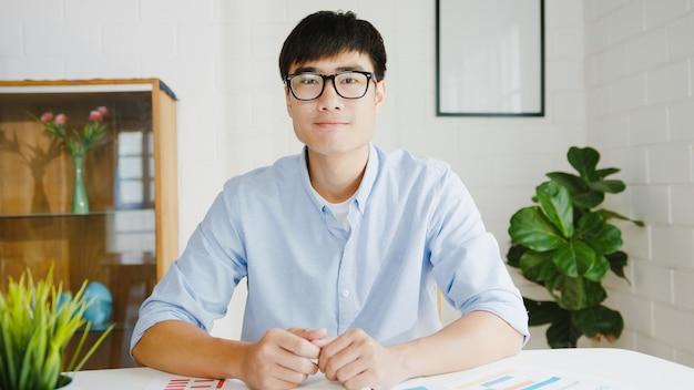 Jonge aziatische zakenman met behulp van computer laptop praten met collega's over plan in videogesprek vergadering tijdens het werken vanuit huis in de woonkamer. zelfisolatie, sociale afstand nemen, quarantaine voor coronavirus.
