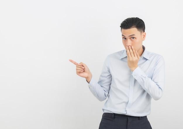 Jonge aziatische zakenman met blauw die overhemd met handen wordt opgewekt die mond behandelen op wit wordt geïsoleerd