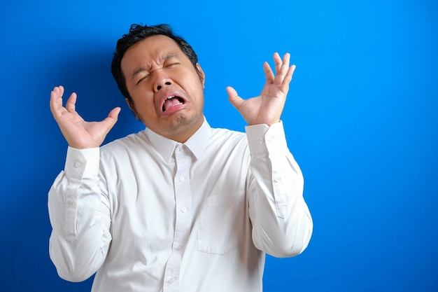 Jonge aziatische zakenman schreeuwen, boze uitdrukking. stressfrustratie in bedrijfsconcept