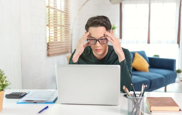 Jonge aziatische zakenman stressvolle tijd werken op laptop thuis. werk vanuit huis concept.
