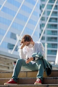 Jonge aziatische zakenman zit verdrietig werkloosheid in crisis covid-19 een lege portemonnee in de handen van een jonge aziatische man.