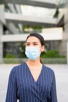 Jonge aziatische zakenvrouw denken met masker voor bescherming tegen de uitbraak van het coronavirus in de stad