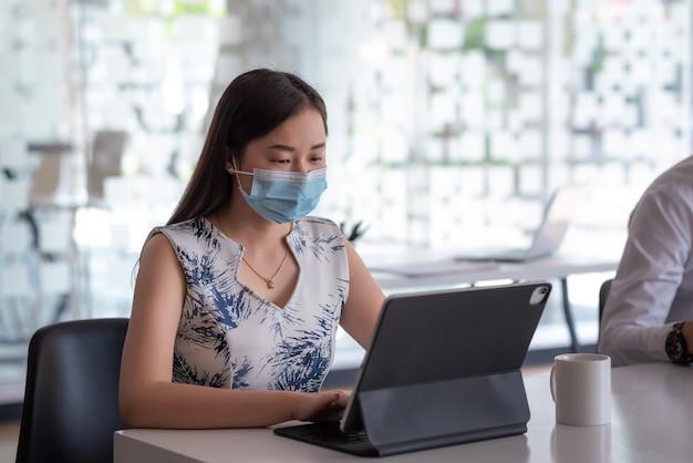 Jonge aziatische zakenvrouw die aan een tablet werkt terwijl ze een masker draagt om te beschermen tegen ziektekiemen op kantoor.
