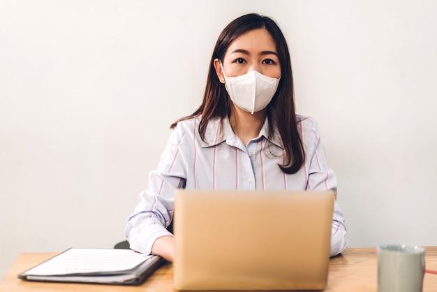 Jonge aziatische zakenvrouw die een laptopcomputer gebruikt die werkt en een vergadering plant in quarantaine voor coronavirus die een beschermend masker draagt met sociale afstand terwijl ze op een bureau zit