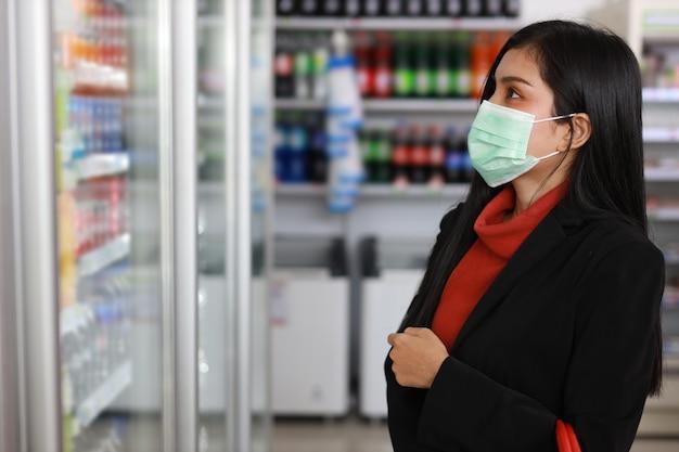 Jonge aziatische zakenvrouw die gezichtsmasker draagt en kruidenierswinkel kiest om te kopen van de plank in het warenhuis van de supermarkt of het winkelcentrum