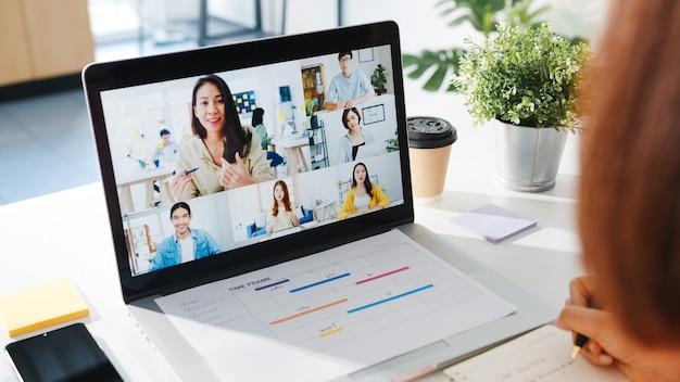 Jonge aziatische zakenvrouw die laptop gebruikt, praat met collega over plan in videogesprekvergadering terwijl ze vanuit huis in de woonkamer werkt.