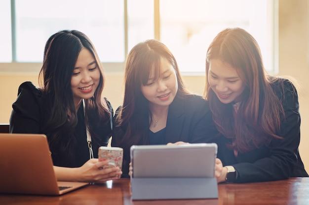 Jonge aziatische zakenvrouw die op een tabletcomputer op kantoor werkt