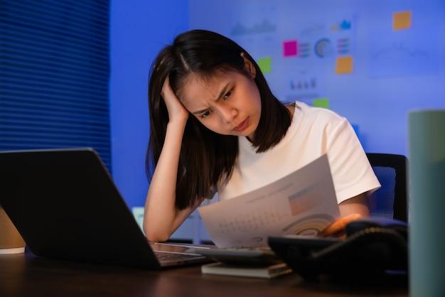 Jonge aziatische zakenvrouw die op laptop werkt met hoofdpijn omdat ze 's nachts op kantoor migraine heeft.